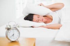 Orelhas da coberta da mulher com descanso e despertador na tabela lateral Fotografia de Stock Royalty Free