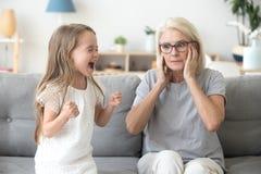 Orelhas de fechamento chocadas da avó para não ouvir a neta teimoso imagem de stock