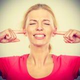 Orelhas de fechamento da mulher com dedos, ruído grande Fotos de Stock