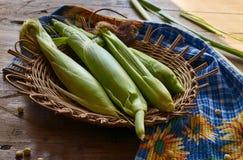 Orelhas de milho em uma cesta na tabela de madeira imagens de stock royalty free