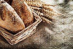 Orelhas do trigo de pão da cesta de vime no fundo de serapilheira Imagens de Stock
