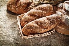 Orelhas do trigo do palito do pão da cesta de vime na parte traseira de serapilheira do vintage Imagem de Stock Royalty Free