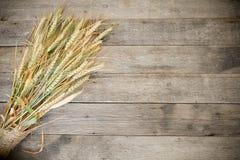 Orelhas do trigo no fundo de madeira rústico Orelhas do trigo no fundo de madeira rústico Fundo das orelhas de amadurecimento do  Fotos de Stock Royalty Free