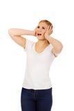 Orelhas irritadas da coberta da jovem mulher com mãos Imagens de Stock
