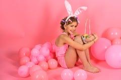 Orelhas vestindo do coelho da menina que guardam a cesta com ovos da páscoa imagens de stock