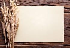 Oren van tarwe en blad van document op oud hout. Stock Fotografie
