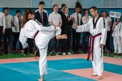 Orenburg, Rusia - 23 de abril de 2016: Las piernas de los fingeres de la muchacha del Taekwondo sacan una taza del lápiz Foto de archivo libre de regalías
