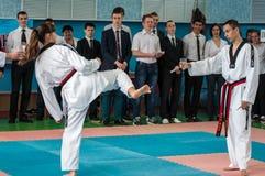 Orenburg, Rusia - 23 de abril de 2016: Las piernas de los fingeres de la muchacha del Taekwondo sacan una taza del lápiz Imágenes de archivo libres de regalías