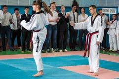 Orenburg, Rusia - 23 de abril de 2016: Las piernas de los fingeres de la muchacha del Taekwondo sacan una taza del lápiz Fotografía de archivo