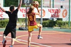 Orenburg, Rusia - 30 de julio de 2017 año: Baloncesto de la calle del juego de las muchachas y de los muchachos Foto de archivo