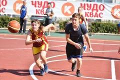 Orenburg, Rusia - 30 de julio de 2017 año: Baloncesto de la calle del juego de las muchachas y de los muchachos Imagenes de archivo
