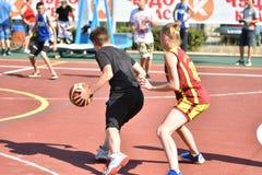 Orenburg, Rusia - 30 de julio de 2017 año: Baloncesto de la calle del juego de las muchachas y de los muchachos Imagen de archivo libre de regalías