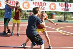 Orenburg, Rusia - 30 de julio de 2017 año: Baloncesto de la calle del juego de las muchachas y de los muchachos Imagen de archivo