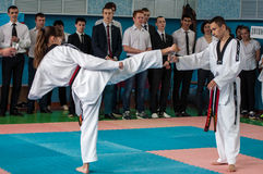 Orenburg, Russia - 23 April 2016: Taekwondo girl fingers legs pulls out a pencil Cup Royalty Free Stock Photo