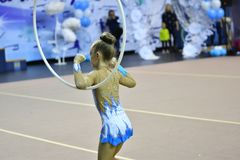 Orenburg, Russia - November 25, 2017 year: girl performs exercises with gymnastic hoop in rhythmic gymnastics Royalty Free Stock Photography