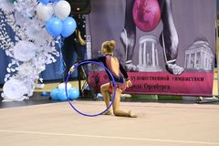 Orenburg, Russia - November 25, 2017 year: girl performs exercises with gymnastic hoop in rhythmic gymnastics Royalty Free Stock Photo
