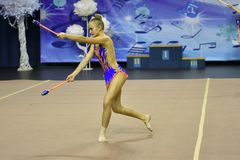 Orenburg, Russia - November 25, 2017 year: girls compete in rhythmic gymnastics perform exercises with sports clubs Stock Photo