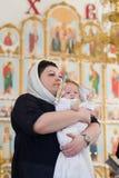 Orenburg, russisches Federation-2 Aprel 2019 Frau, die ein Baby während des Tauferituals hält stockbild