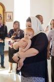 Orenburg, russo Federation-2 Aprel 2019 Mulher que guarda um bebê durante o ritual do batismo foto de stock royalty free
