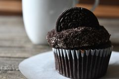 Oreo cupcake on the wood background. Coffee break , we love Oreo cupcake and black coffee so delicious Stock Image