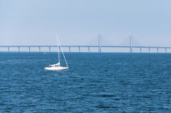 The Oresund bridge, seen from Malmo, Sweden. The Oresund bridge, with a yacht in front of it, in a sunny day, seen from Malmo, Sweden Stock Photography