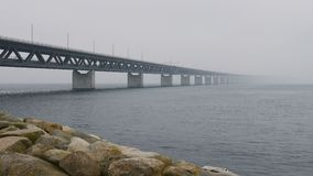 Oresundsbron, the bridge between Sweden and Denmark a foggy day. Cars drive over the bridge and underneath the bridge goes a train stock video