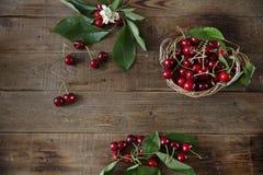 Orgánico fresco una rama de cerezas dulces con hojas verdes en el fondo rústico de madera Concepto sano del alimento Visi?n super fotografía de archivo libre de regalías