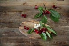 Org?nico fresco una rama de cerezas dulces con hojas verdes en el fondo r?stico de madera Concepto sano del alimento Visi?n super fotos de archivo