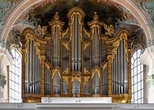 Organ in a church with silver pipes and golden ornaments royalty free stock photos