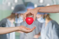Organ donation concept. Hand giving heart. Surgeons in background Stock Image