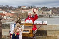An organ grinder player on Charles bridge, Prague Stock Photo