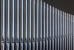 Organ pipes. Row of shiny silver organ pipes diminishing in size Royalty Free Stock Photo
