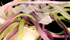 Organdy and Grosgrain Ribbons. Assorted organdy and grosgrain ribbons coiled and laying on a black background Stock Photo