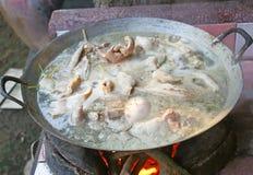 Organe des porcs sur le pot de l'eau Boiled sur le fourneau avec le bois de chauffage photographie stock libre de droits