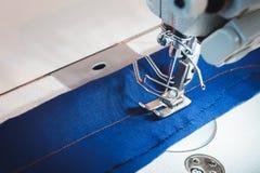 Organe mobile de machine à coudre avec le tissu bleu Photo stock