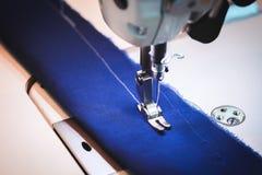Organe mobile de machine à coudre avec le tissu bleu Image stock