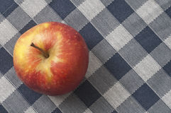 Organic apple on chequered tablecloth Stock Photos