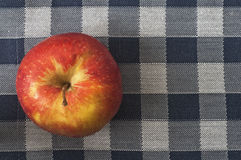Organic apple on chequered tablecloth Royalty Free Stock Photos