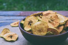 Organic apple chips. Dried fruits. Healthy sweet snack. Dehydrated and raw food. Copy space royalty free stock photo