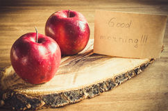 Organic apples and Good morning note on rustic wooden background. Royalty Free Stock Photography