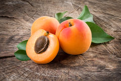 Organic apricots with leaves on wooden background. Organic apricots with leaves  on wooden background Royalty Free Stock Image