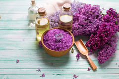 Organic aroma oils, sea salt,  lilac flowers. Spa setting. Organic aroma oils, sea salt,  lilac flowers  on turquoise painted wooden planks. Selective focus Royalty Free Stock Photos