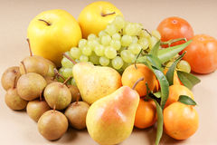 Organic autumn fruits. Assortment of autumn fruits: wild european pears, apples, Williams pears, grape, clementines and asian persimmons. Studio shot over light Stock Photo