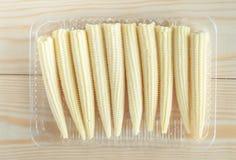 Organic baby corn in plastic container Stock Photos