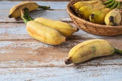 Organic banana in basket. On wooden table royalty free stock images