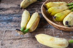 Organic banana in basket. On wooden table stock images
