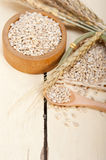 Organic barley grains. Over rustic wood table macro closeup Stock Photos