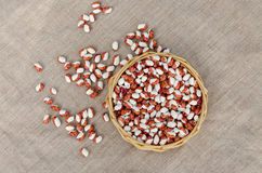 Organic beans in wicker basket on linen texture Royalty Free Stock Photo
