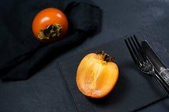 Organic bio persimmon on black background. stock photography