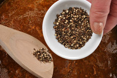 Organic black pepper into a sauce Stock Image